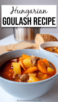 blue bowl of Hungarian goulash on white table with bread in background