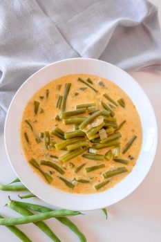 white bowl with orange hungarian green bean soup on table with beans beside