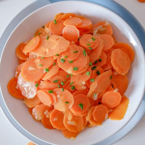bowl of german carrot salad on white table