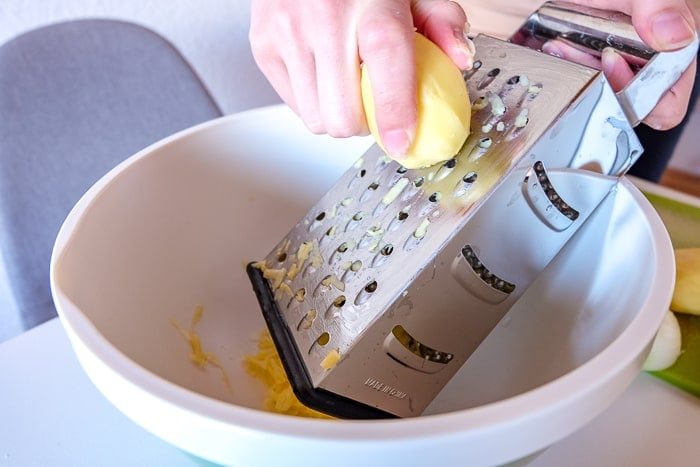potato held in hand grated using grater into bowl