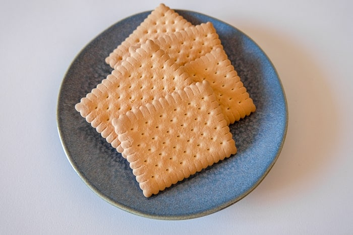 square butter biscuits on blue plate on white table