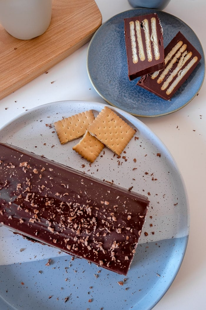 chocolate cake on blue plate with slices and cookies beside kalter hund