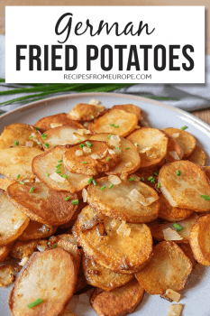 Plate full of German fried potatoes garnished with chives and onions with text overlay