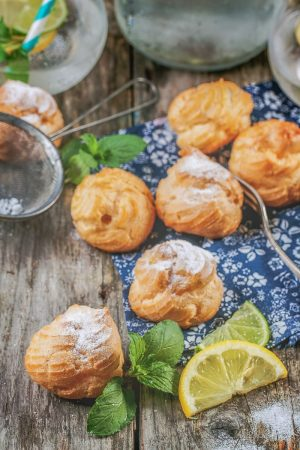 yellow cream puffs pastries on wooden table with lemon slice beside
