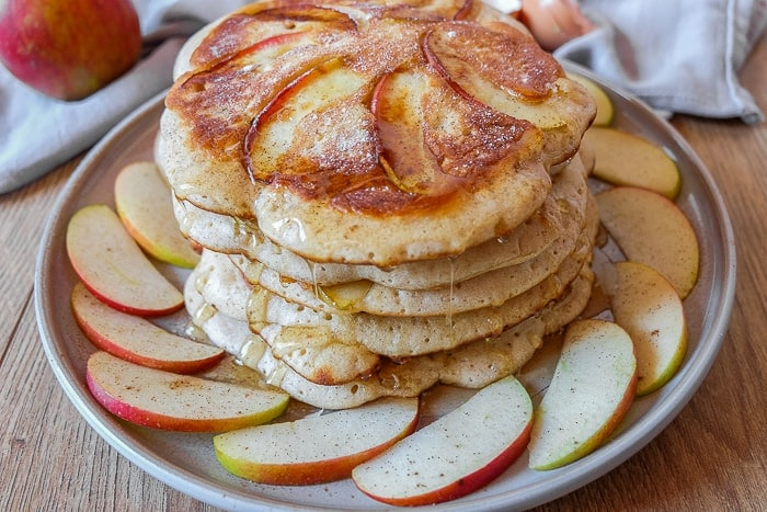 stack of german apple pancakes on plate with sliced apples around on wooden table