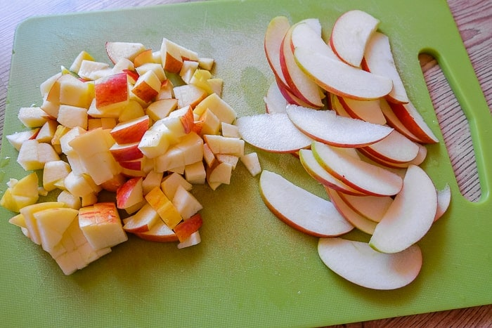 sliced apples and cut up apple pieces on green cutting board