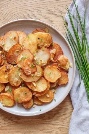 grey plate with german fried potatoes beside green chives on cloth