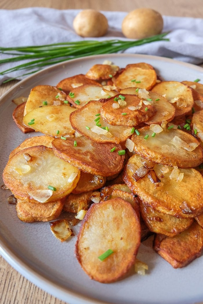 close up shot of german fried potatoes on grey plate with potatoes and chives behind