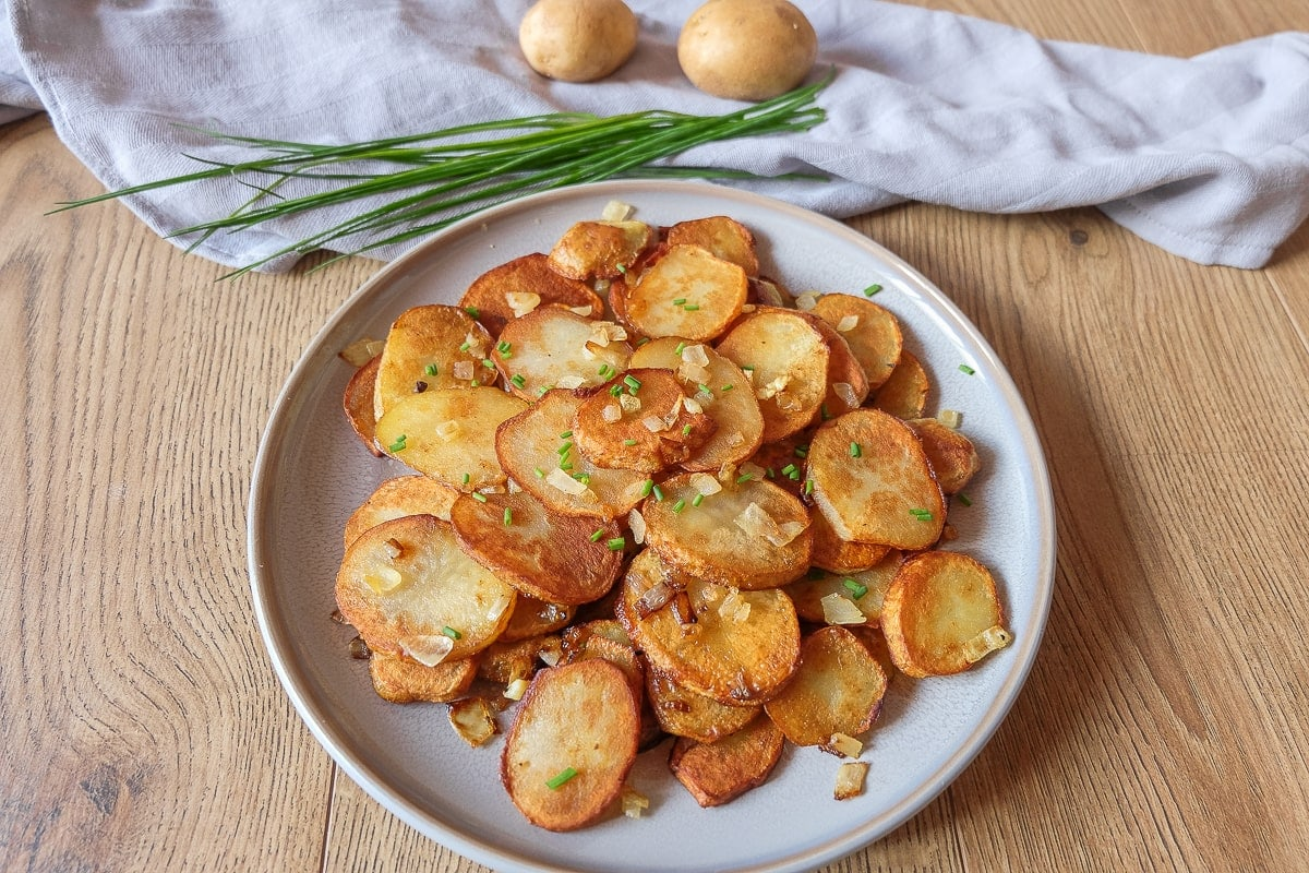 plate of german fried potatoes on wooden table with chives behind