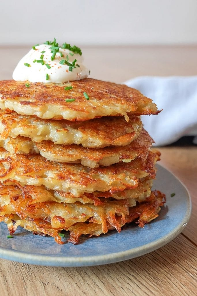 stack of golden brown german potato pancakes with cheese and chives on top