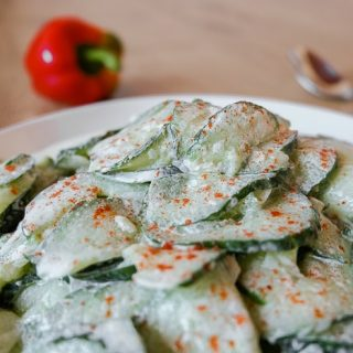 hungarian cucumber salad on bowl with spoon and red pepper behind