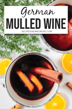 Photo of mulled red wine in mug with cinnamon sticks and organce slices plus text overlay for Pinterest