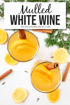 Photo of mulled white wine in glass with cinnamon stick and orange slices plus text overlay for Pinterest