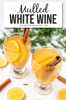Photo of mulled white wine in glass with decoration around plus text overlay for Pinterest