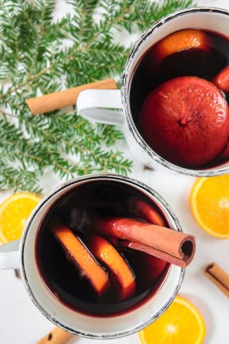 two mugs of german mulled wine with oranges and cinnamon around