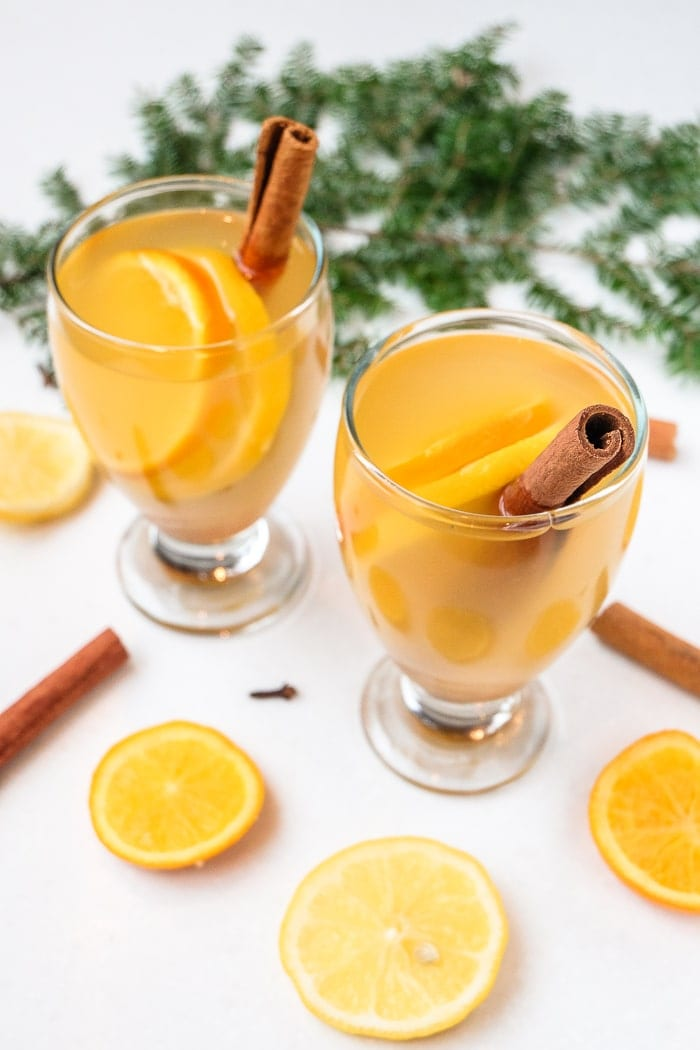 two glasses of mulled white wine on white table with cinnamon