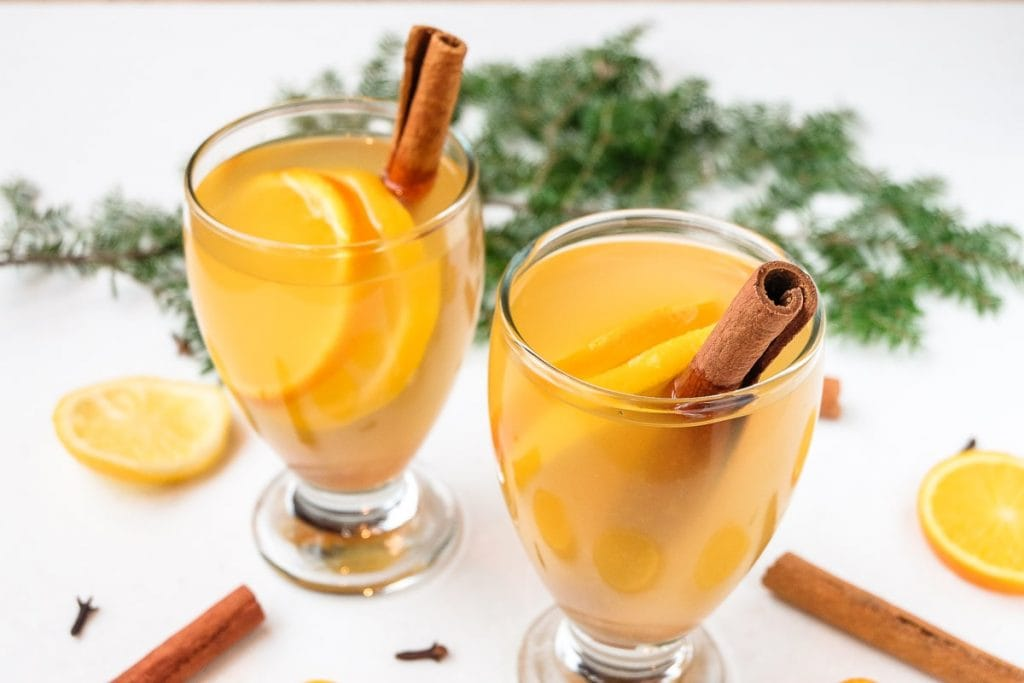 two glasses of mulled white wine with cinnamon sticks around