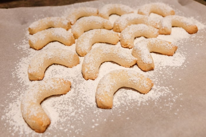 crescent cookies covered in powder sugar on baking sheet