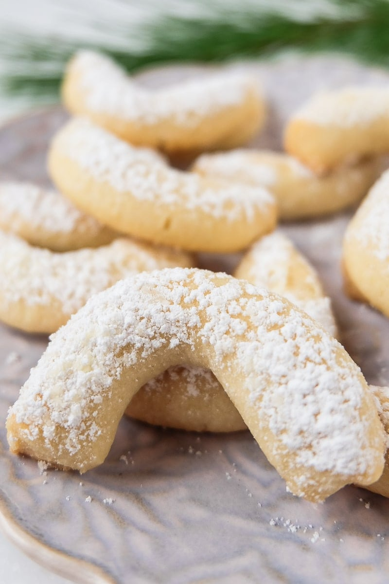 vanilla crescent cookie coated in icing sugar with cookies behind