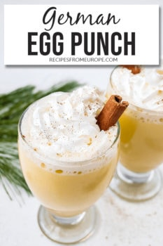 Photo of glasses with egg punch whipped cream and cinnamon stick plus text overlay for Pinterest