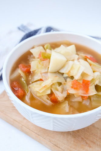 bowl of cabbage potato soup on wooden cutting board