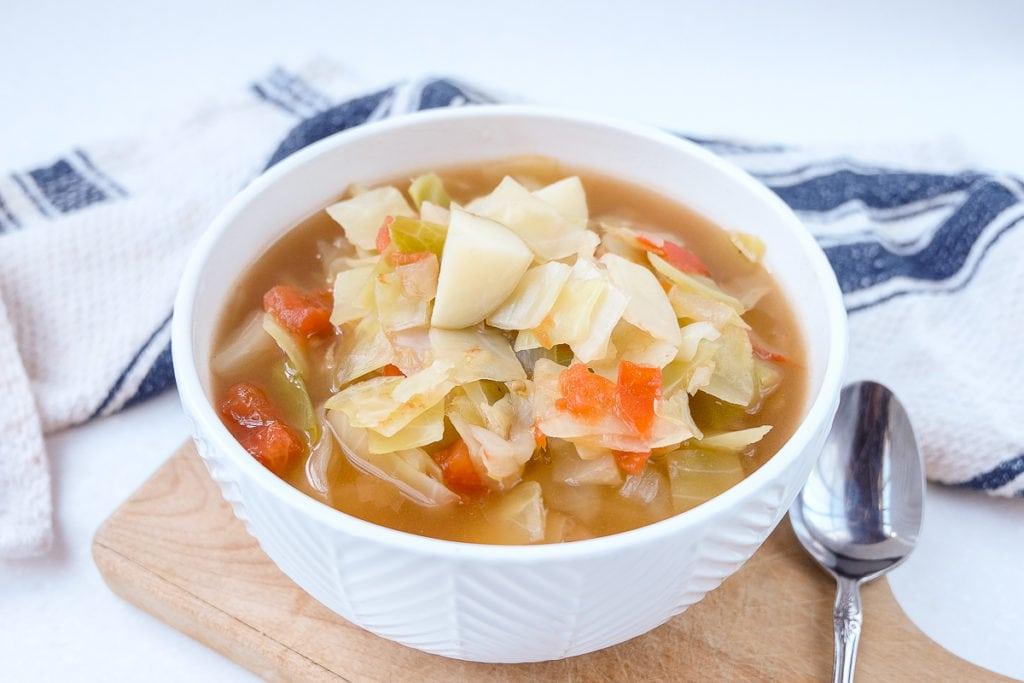 bowl of cabbage potato soup on board with spoon beside