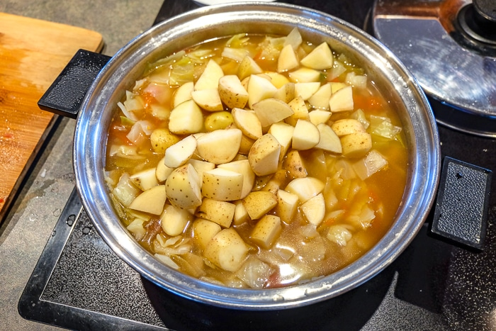 pot of cabbage soup with cut potatoes on top