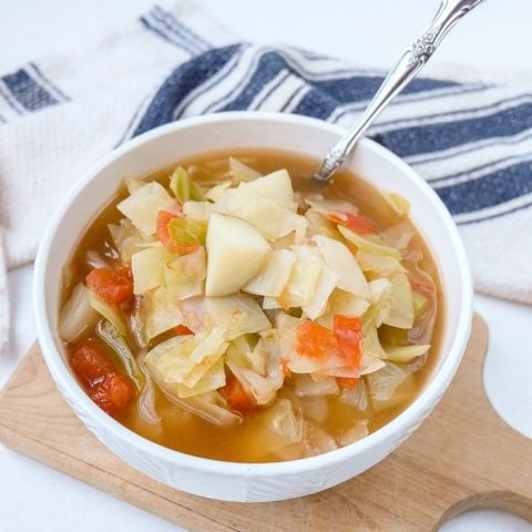 cabbage potato soup in bowl with spoon sticking out