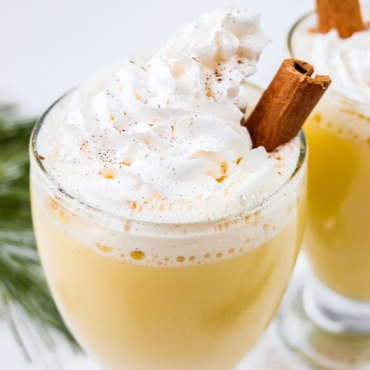 german eierpunsch in glass with cinnamon stick and whipped cream