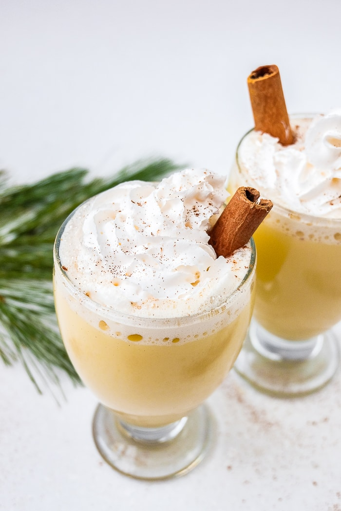 german egg punch in glasses with whopping cream and cinnamon sticks