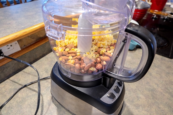 full food processor with nuts and fruit inside
