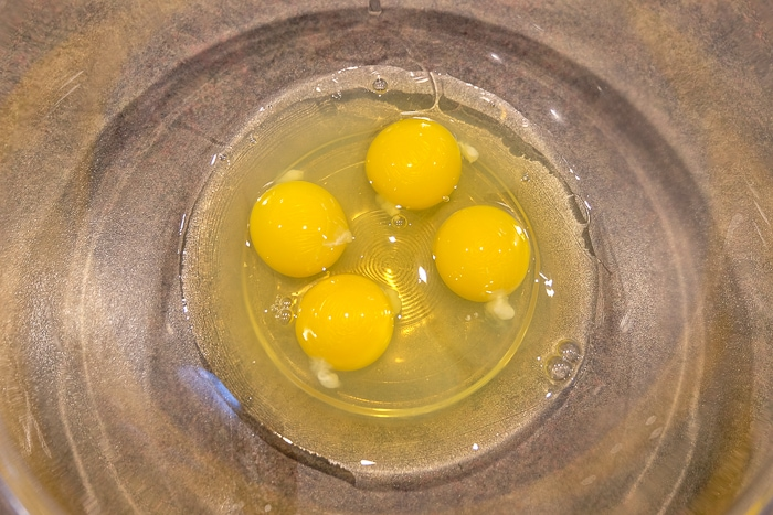 four eggs in clear mixing bowl on counter