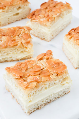 slices of almond covered Bienenstich bee sting cake on white marble counter