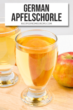 Photo of apple juice and water in two glasses with whole apple in background and text overlay for Pinterest