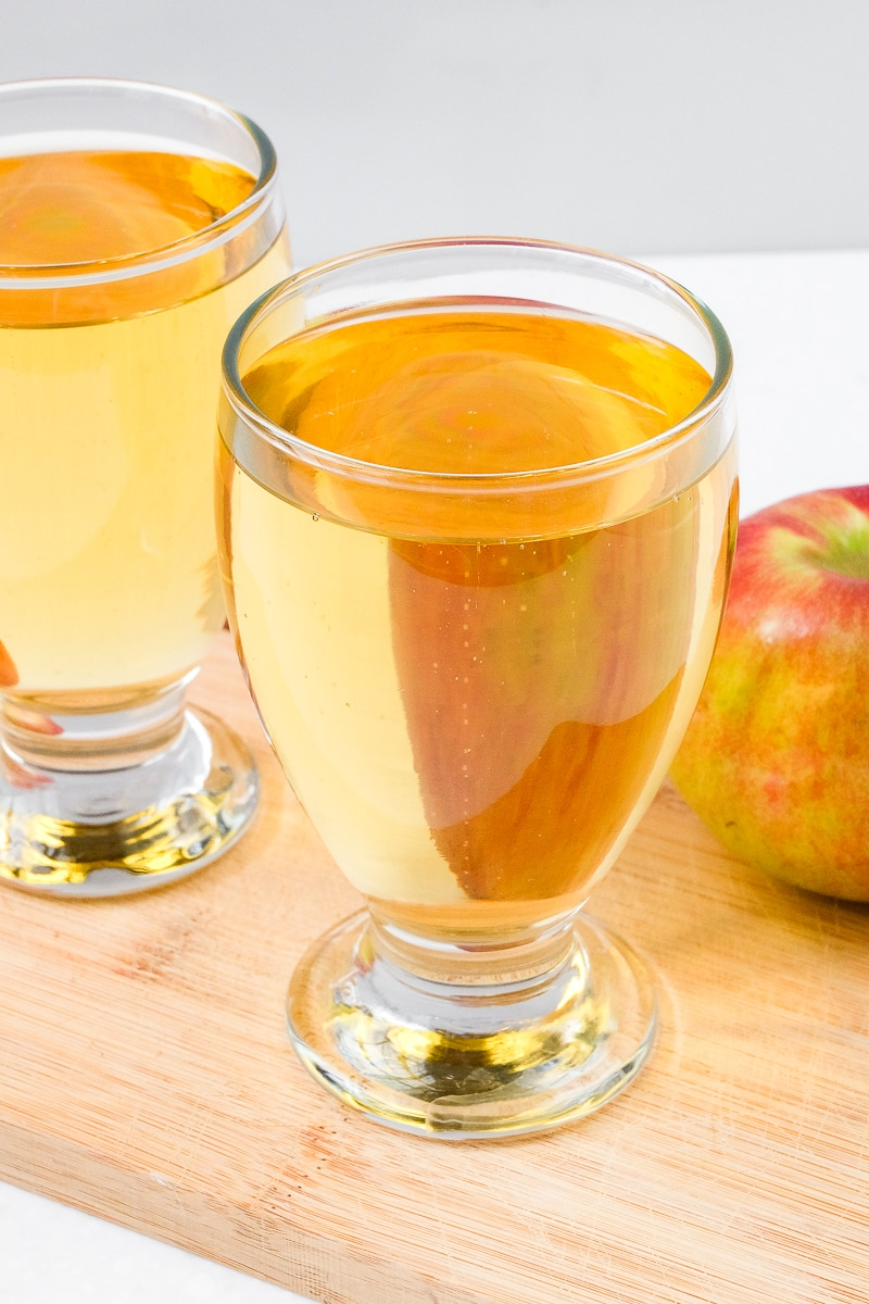 glasses of german apple spritzer with apple sitting beside