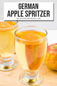 Photo of golden liquid in two glasses with whole apple in background and text overlay for Pinterest