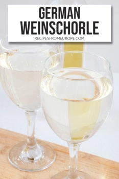 Photo of two glasses with white wine on wooden board with bottle in background and text overlay for Pinterest