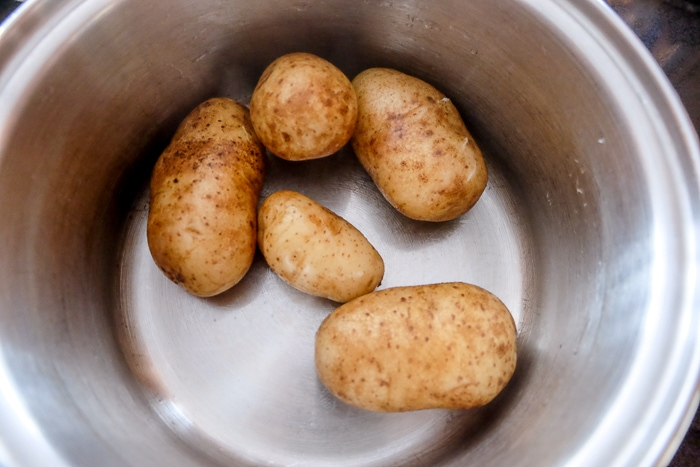 boiled potatoes with skins on in metallic pot