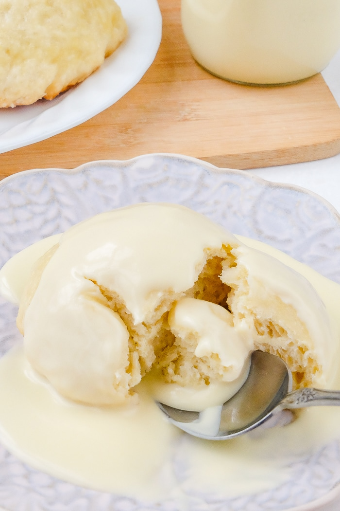 german dampfnudeln with vanilla sauce with spoon cutting it open