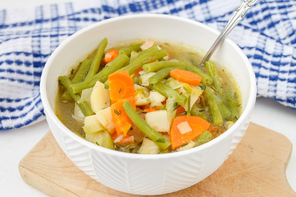 german green bean soup in white bowl with spoon