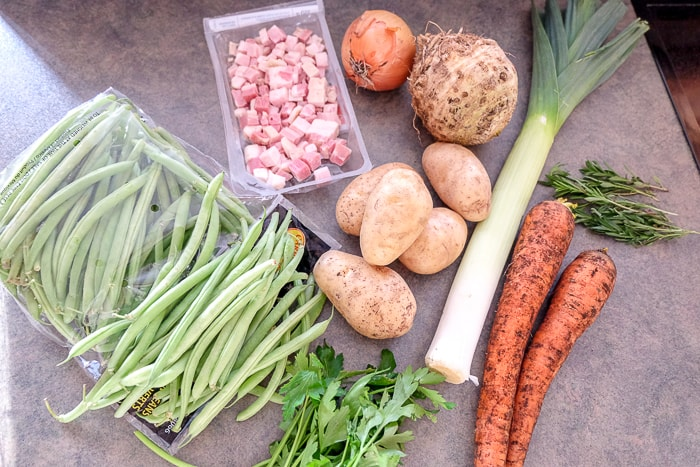 raw vegetables on counter top ready to be chopped into soup