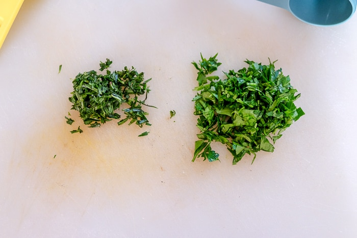 chopped parsley and savory on white cutting board in piles