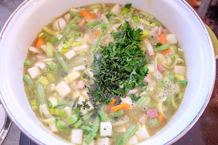 chopped parsley on top of simmering soup in pot on stove