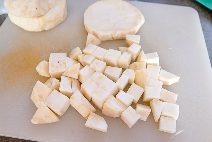 celery root sliced and chopped on white plastic cutting board