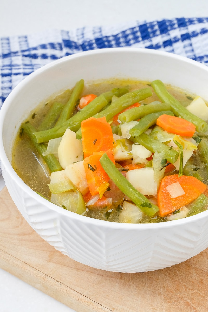 german green bean soup with vegetables in white bowl on wood