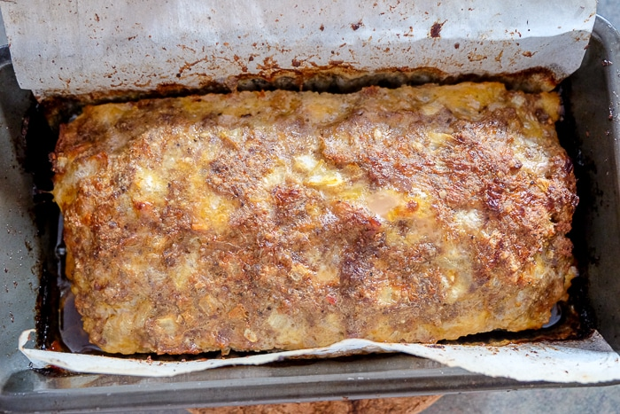 baked german meatloaf in loaf pan with parchment paper around