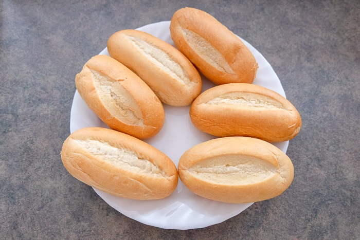six dinner rolls on white plate on counter