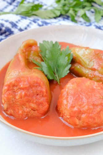 hungarian stuffed peppers in white bowl with parsley
