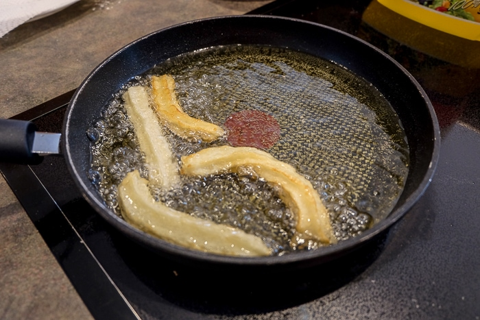 browning spanish churros dough in pan of bubbling oil