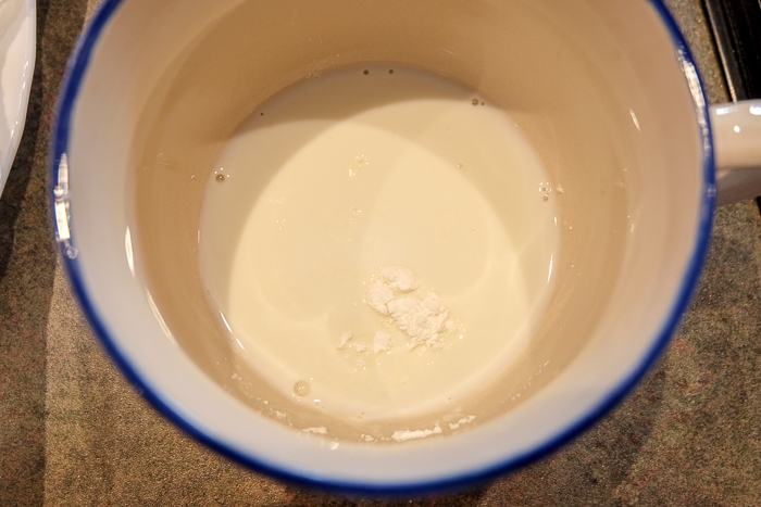 corn starch in milk in mug ready to be mixed
